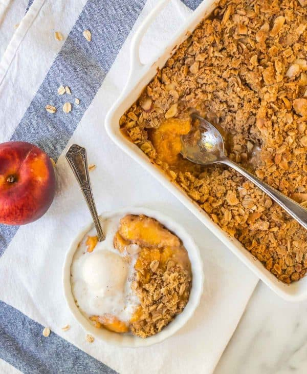 Healthy peach crisp served in a bowl next to a baking dish of peach crisp
