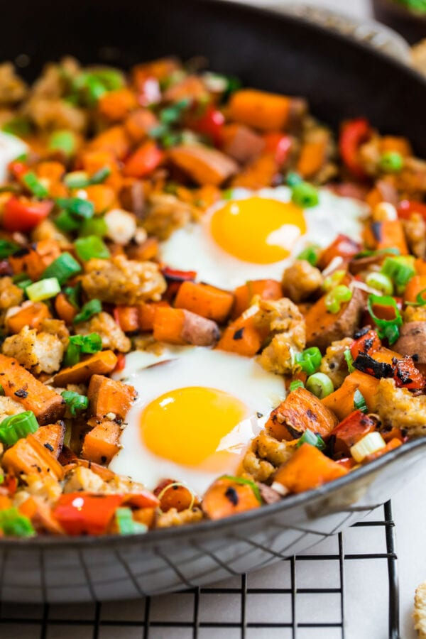a close up of an egg cooked on top of sweet potato hash with sausage and green onion