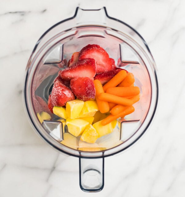 Mango, strawberries, and carrots in a blender