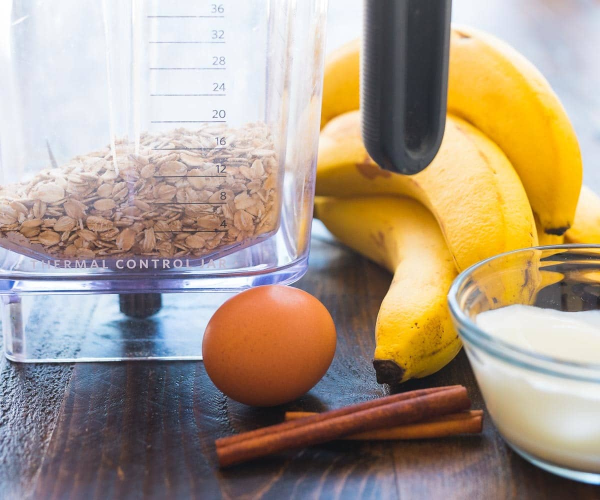 Bananas, eggs, cinnamon, and yogurt on a wooden surface with a blender full of oats