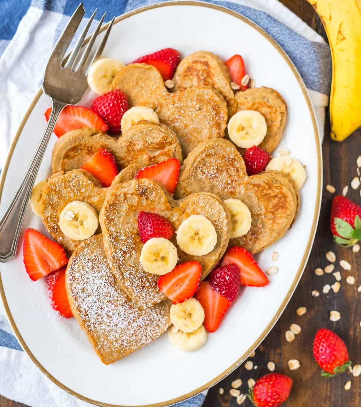 Heart-shaped oatmeal pancakes on a white platter with fresh fruit