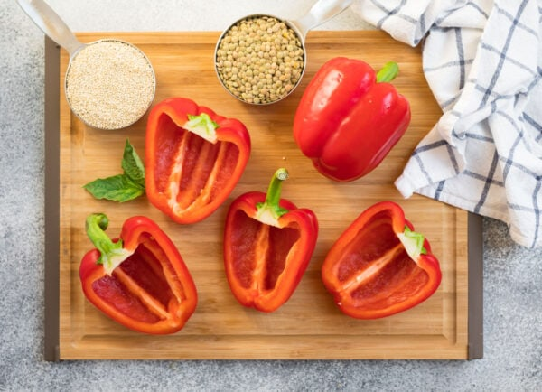 Red bell peppers, lentils, and quiona on a cutting board