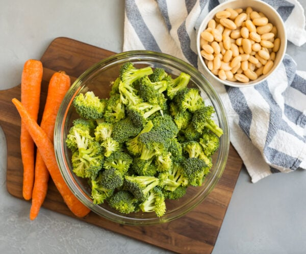 Carrots on a wooden cutting board, and broccoli and beans in bowls