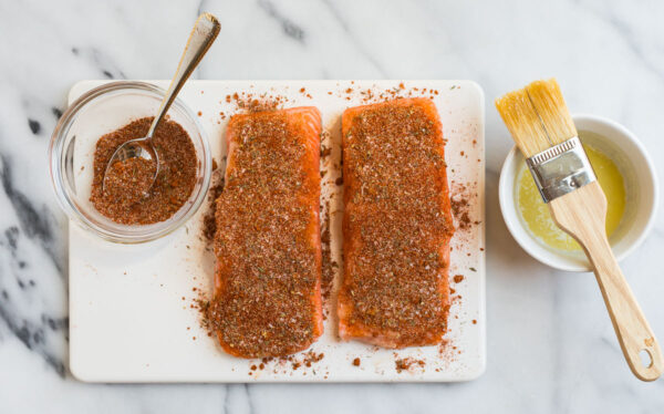 Two pieces of fish being coated in spices