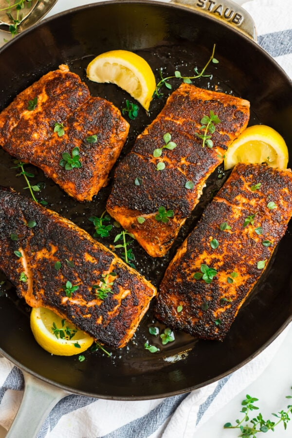 Healthy blackened salmon in a skillet with lemon