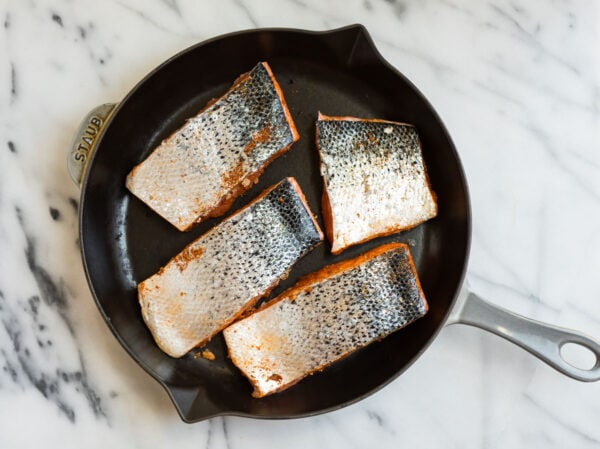 Four pieces of salmon in a skillet skin side up