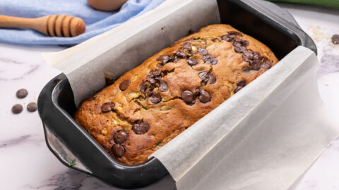 A loaf pan with chocolate chip gluten free zucchini bread