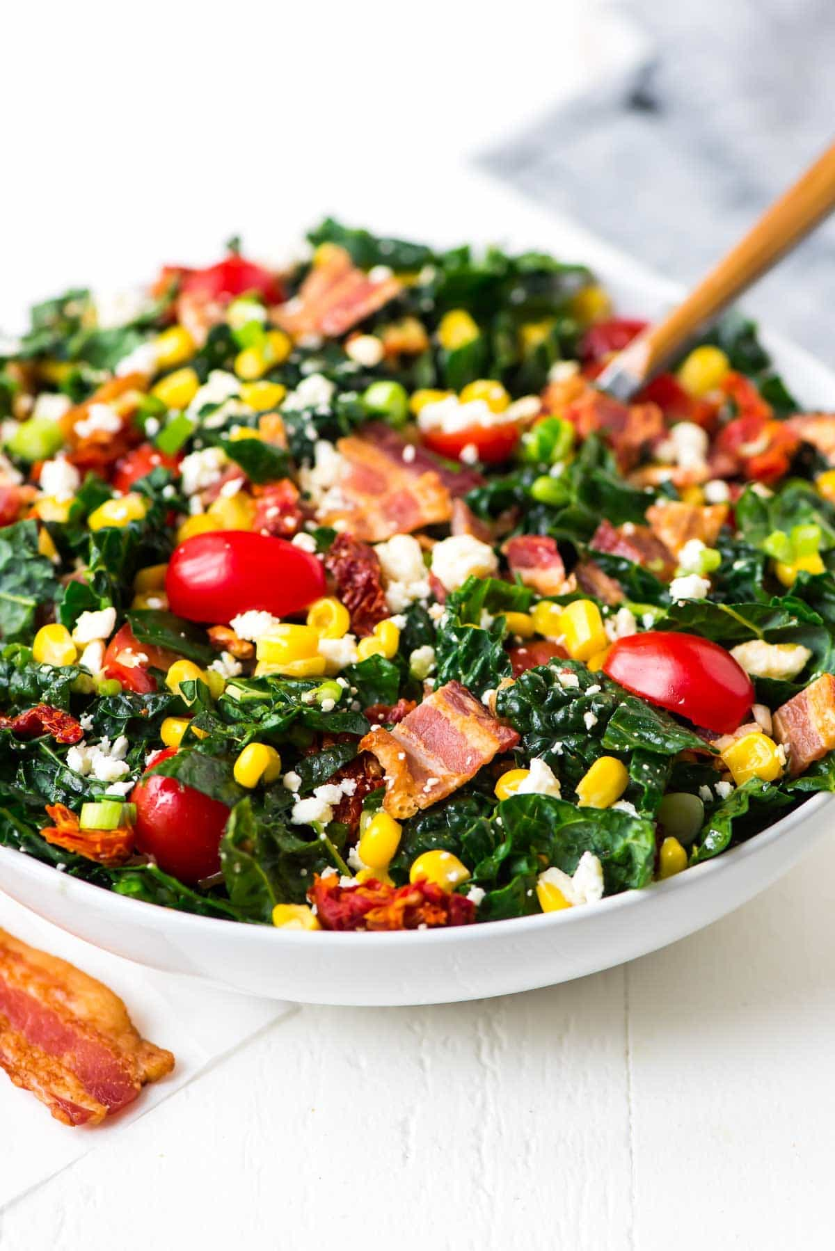 An easy salad in a bowl with bacon, lettuce, tomato, and corn