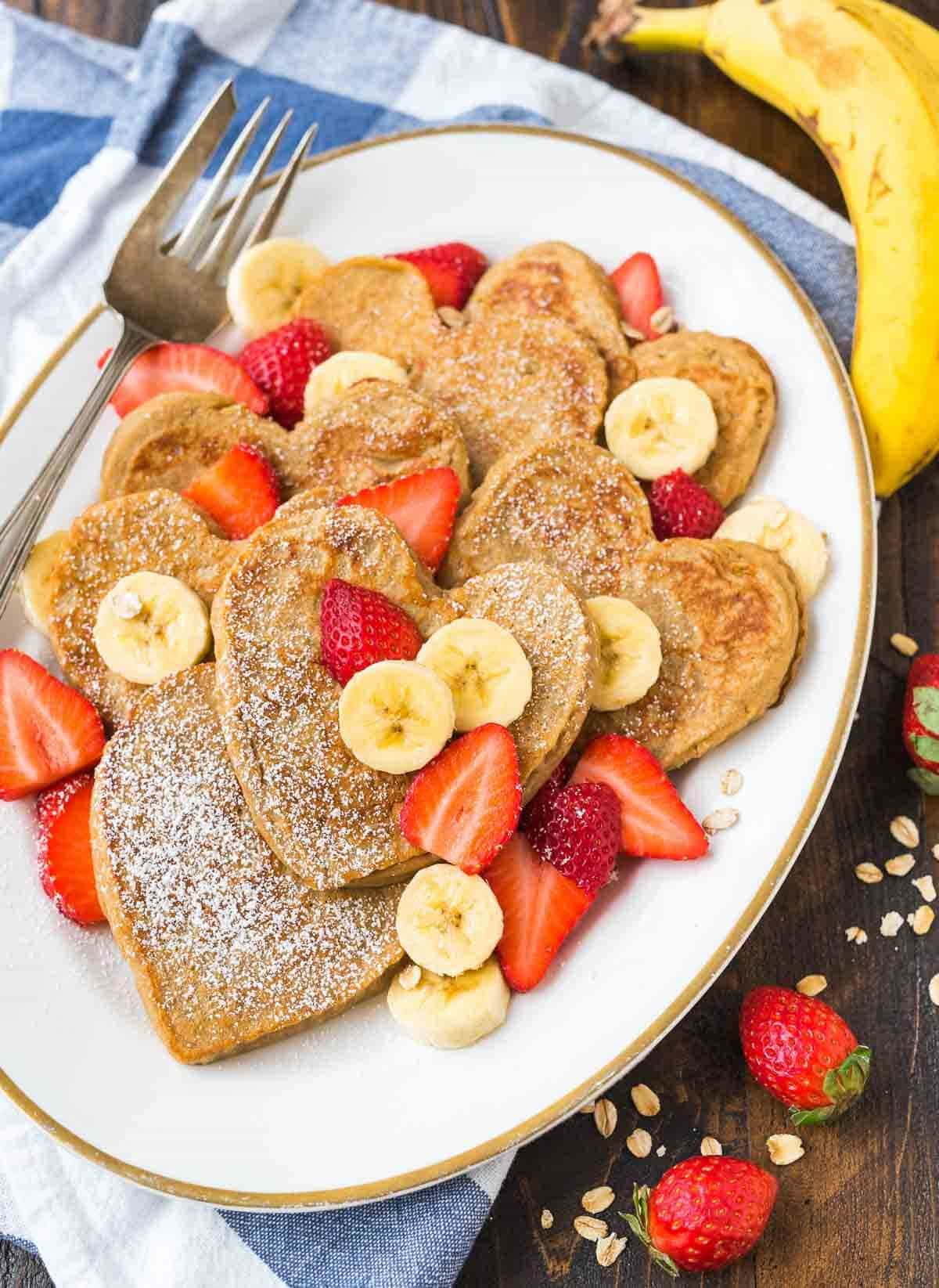 White platter with healthy banana oatmeal pancakes in heart shapes with fresh fruit