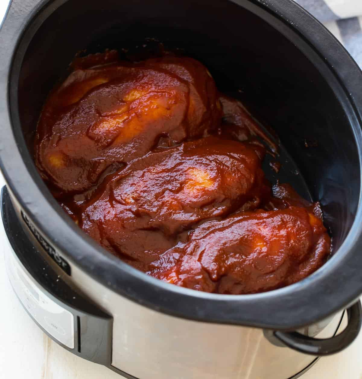 Chicken breasts in a slow cooker with BBQ sauce