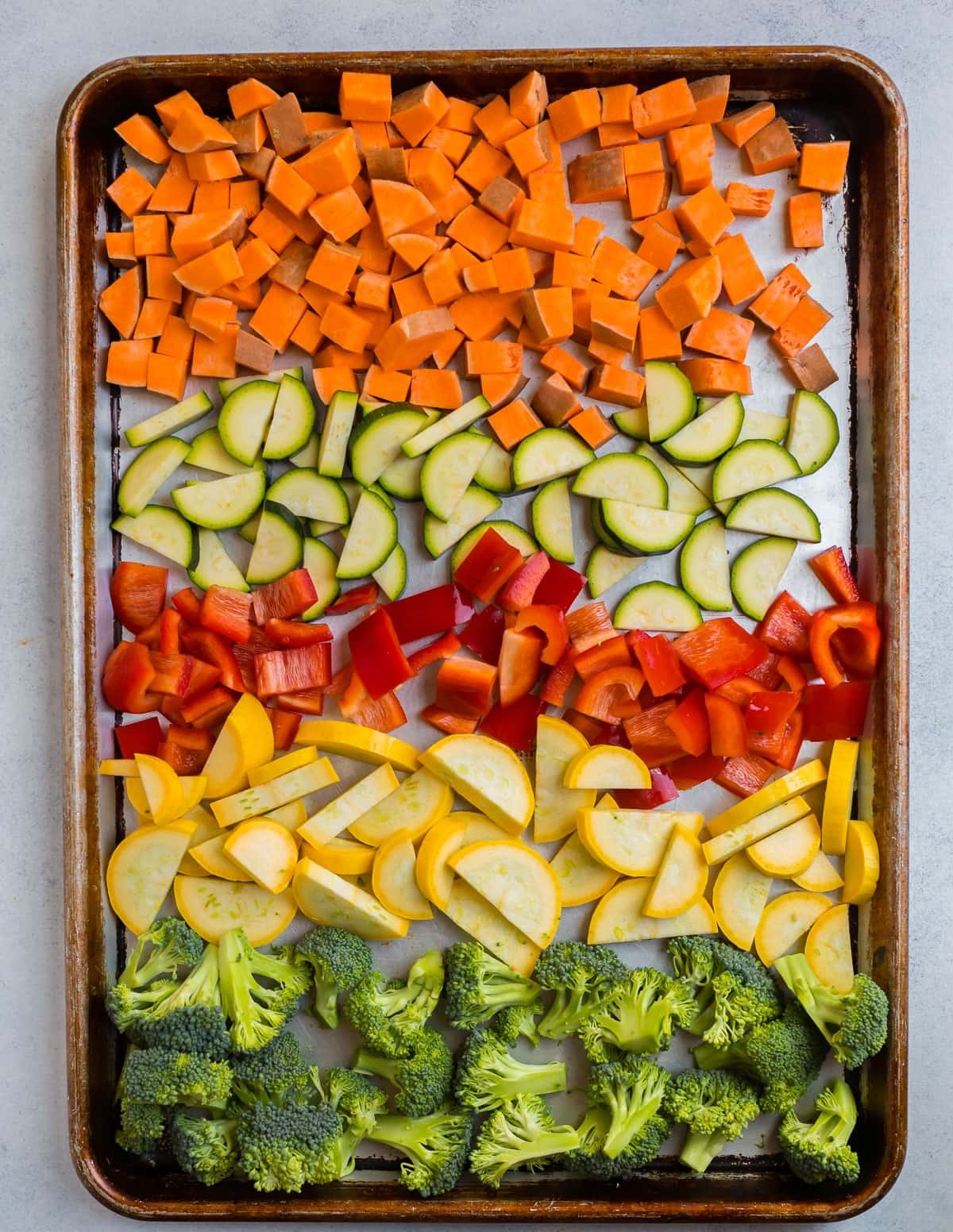 Chopped sweet potatoes, zucchini, peppers, squash, and broccoli on a baking sheet