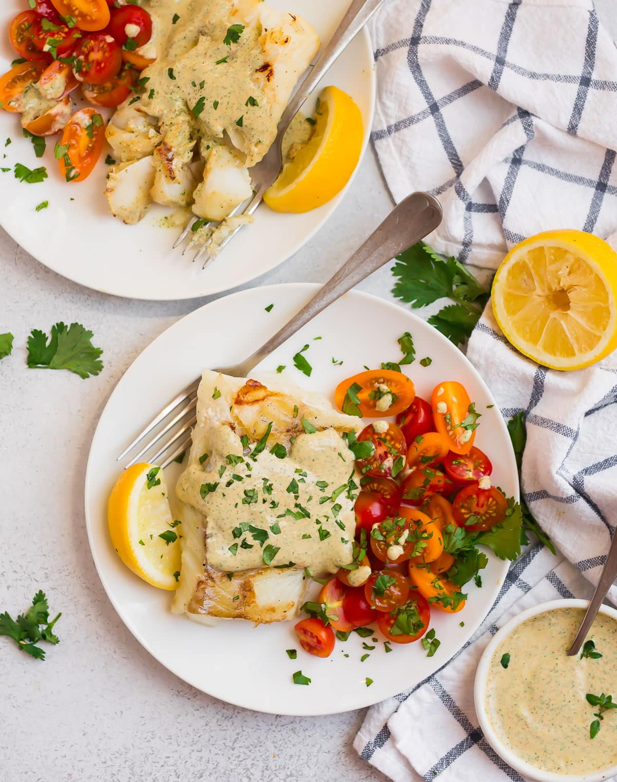 Two plates of grilled cod with lemon and tomatoes