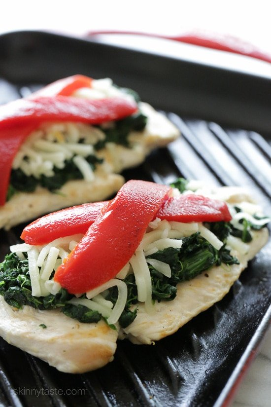 Grilled chicken on a grill pan topped with sauteed garlicky spinach, mozzarella and roasted peppers