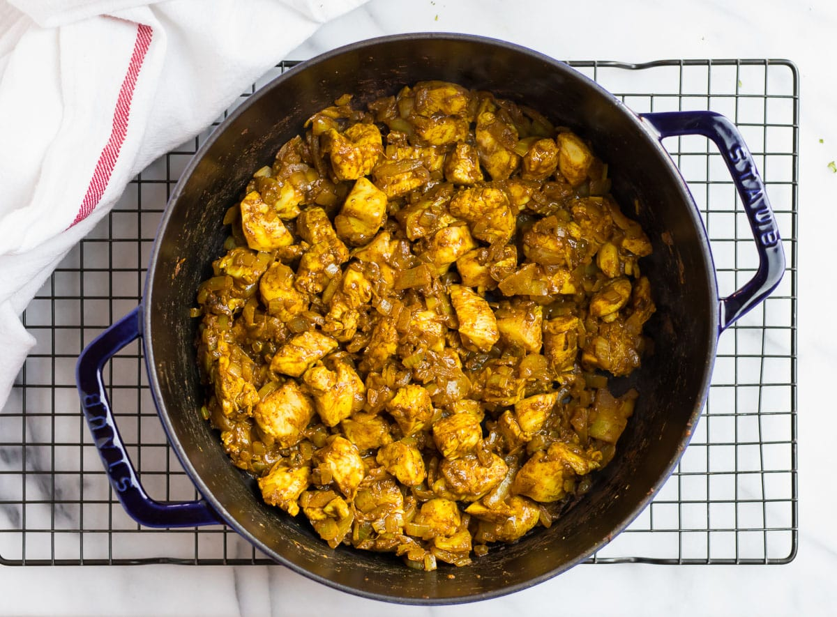 Pieces of chicken, vegetables, and spices in a Dutch oven