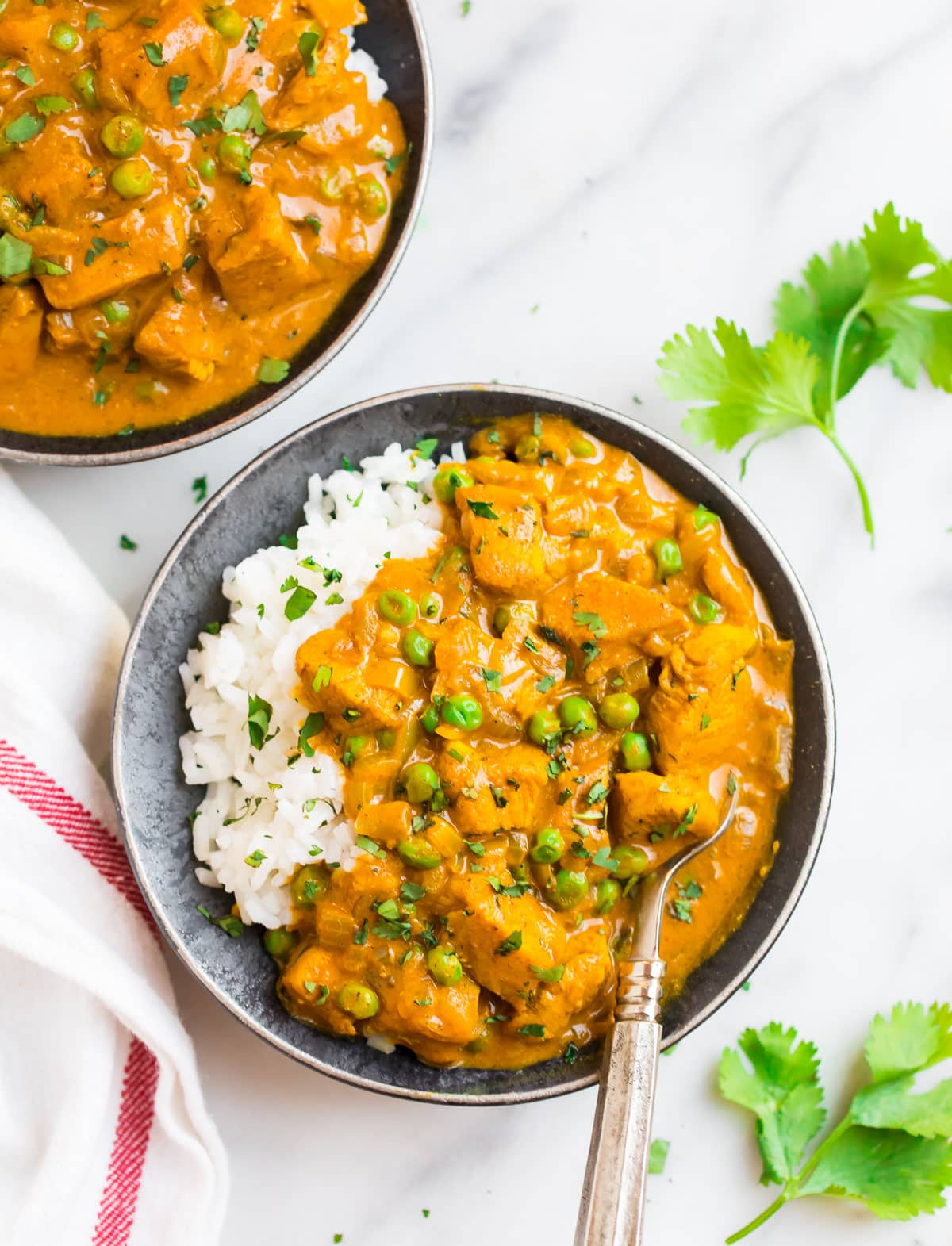 Two bowls of chicken tikka masala with rice