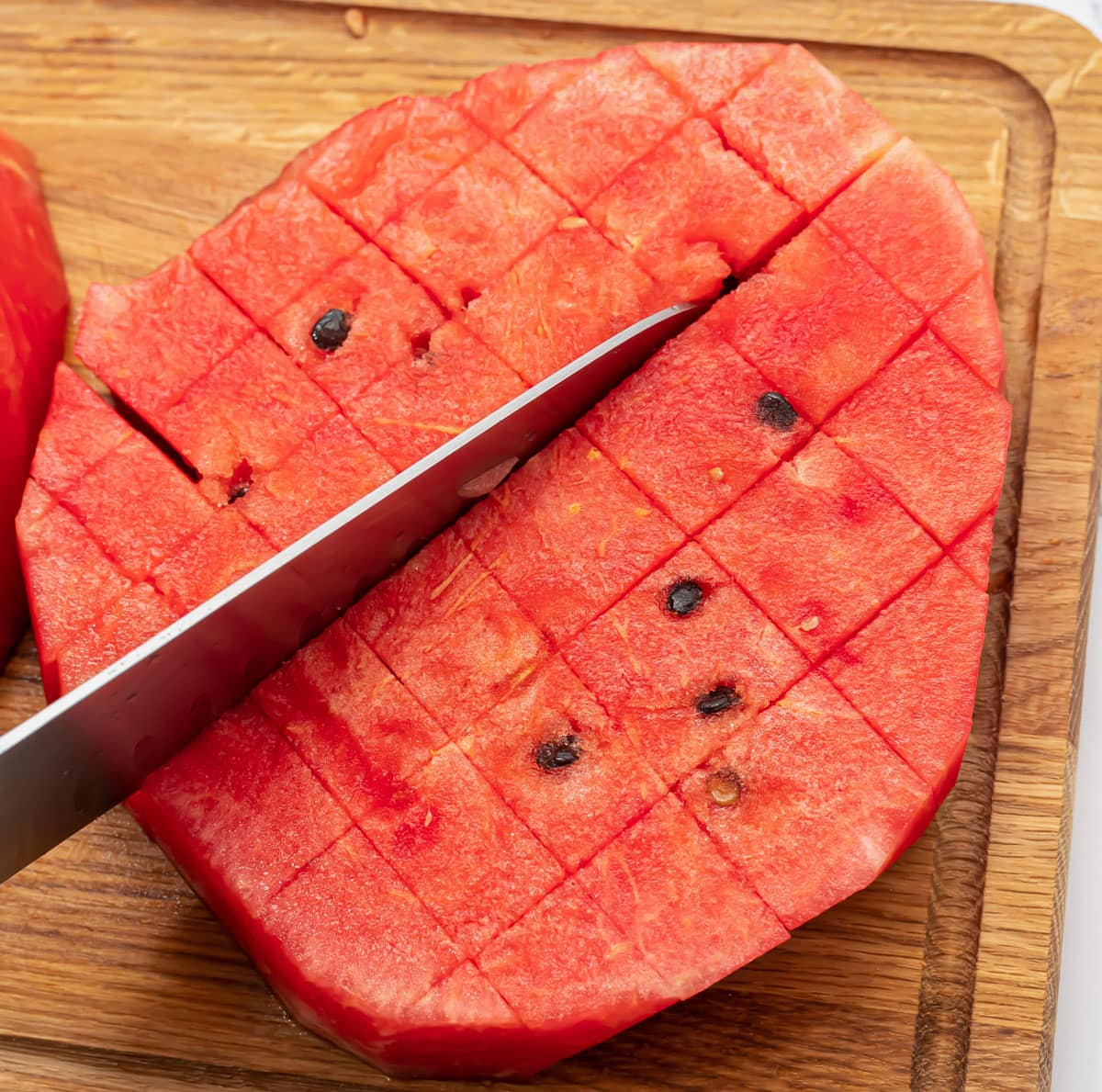 A watermelon being cut into cubes