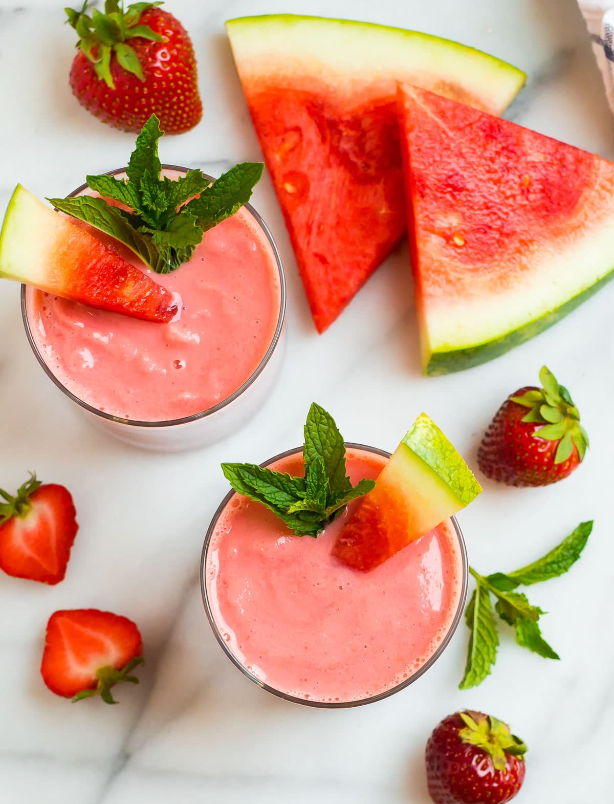 Two watermelon smoothies in glasses next to strawberries and watermelon slices