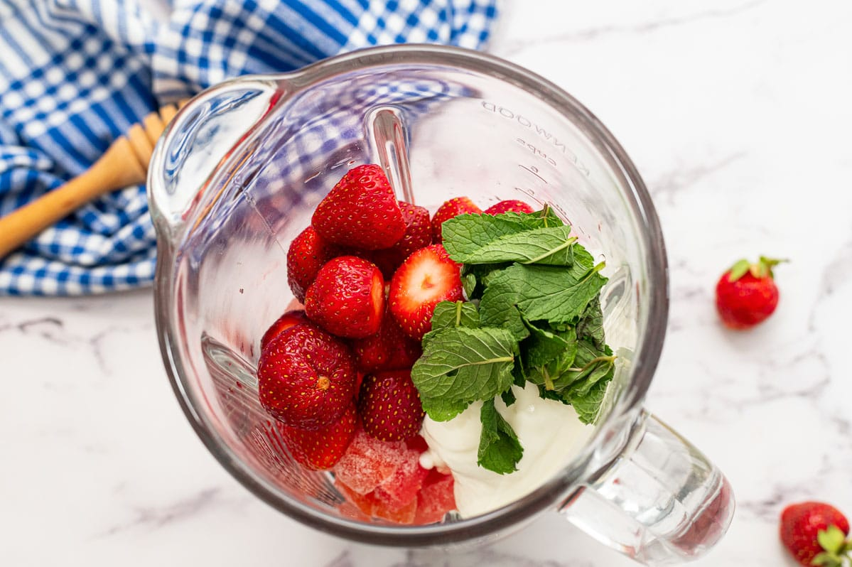 Strawberries, watermelon, and mint in a blender