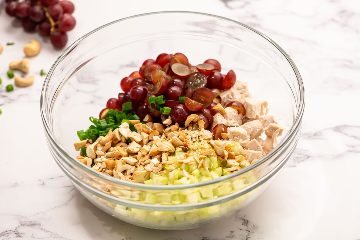 A bowl of ingredients for chicken salad
