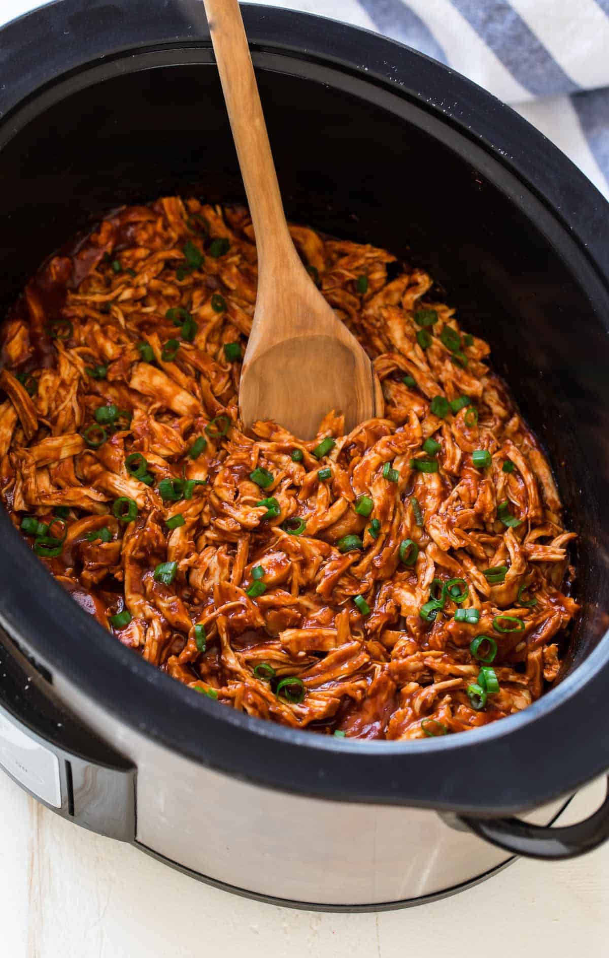Bbq chicken in a slow cooker with green onions