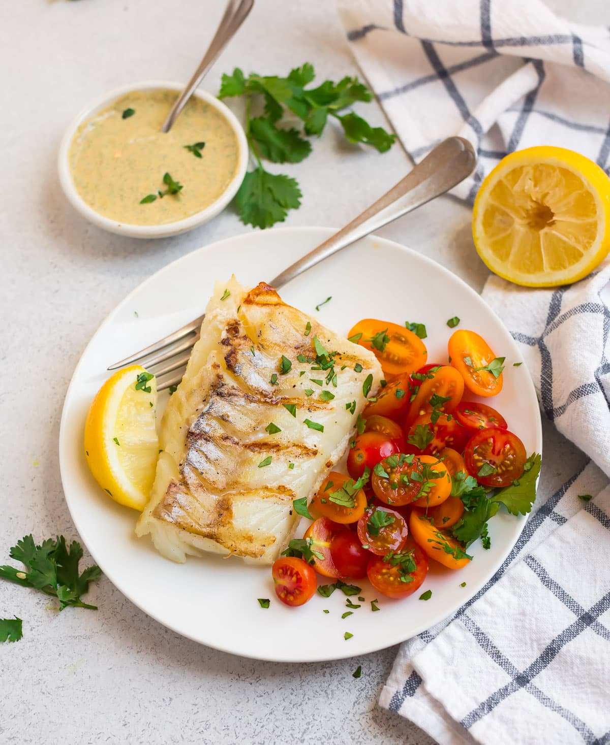 Grilled cod with cilantro yogurt sauce and tomatoes