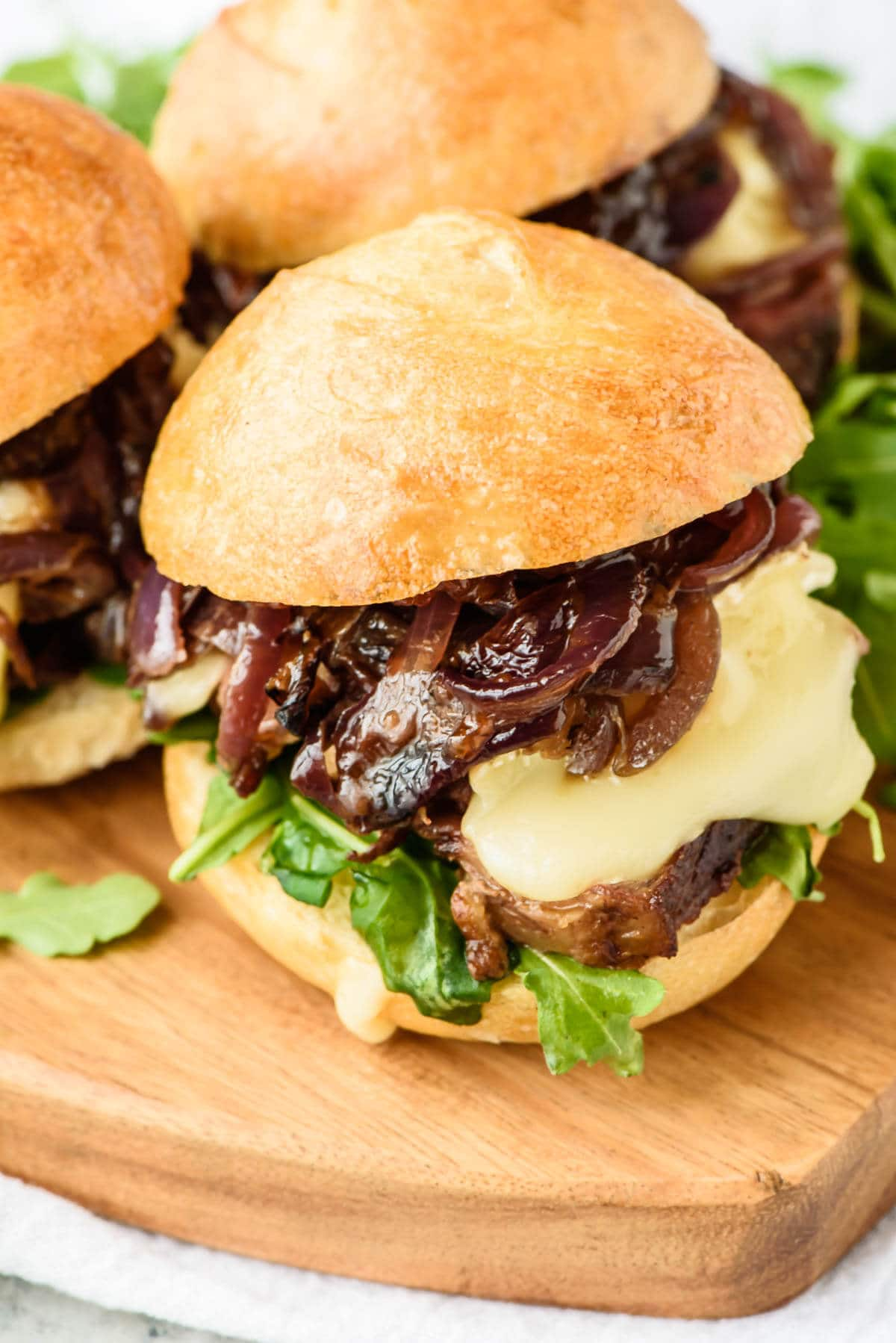 Steak sandwiches on a cutting board with fig jam, Brie, and caramelized onions