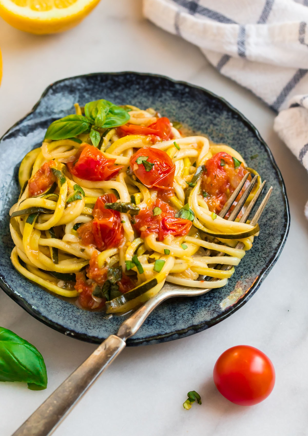 Zucchini pasta on a blue plate with tomatoes