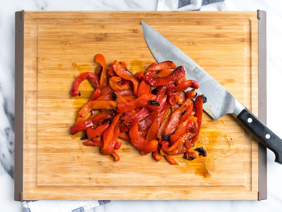 Roasted red peppers being cut on a cutting board