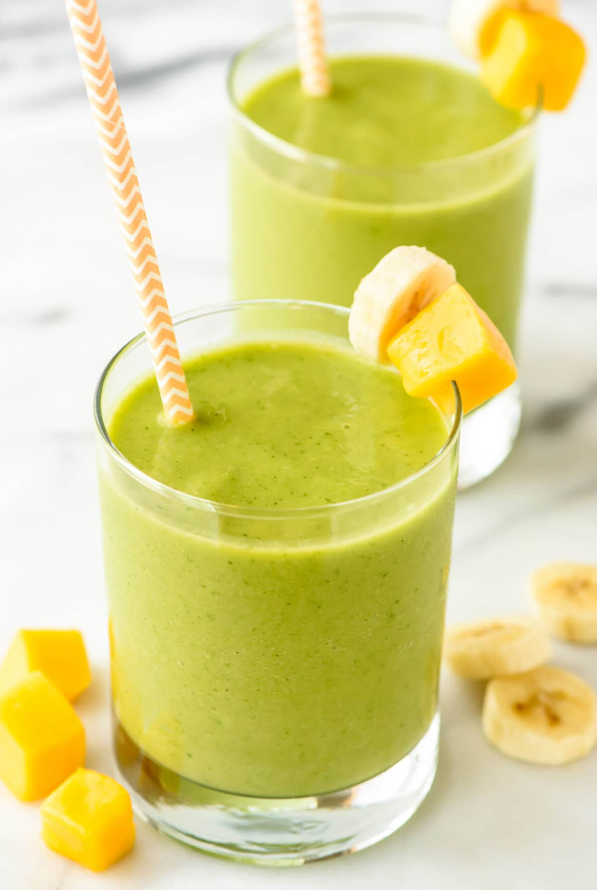 Mango green smoothies in glasses with straws