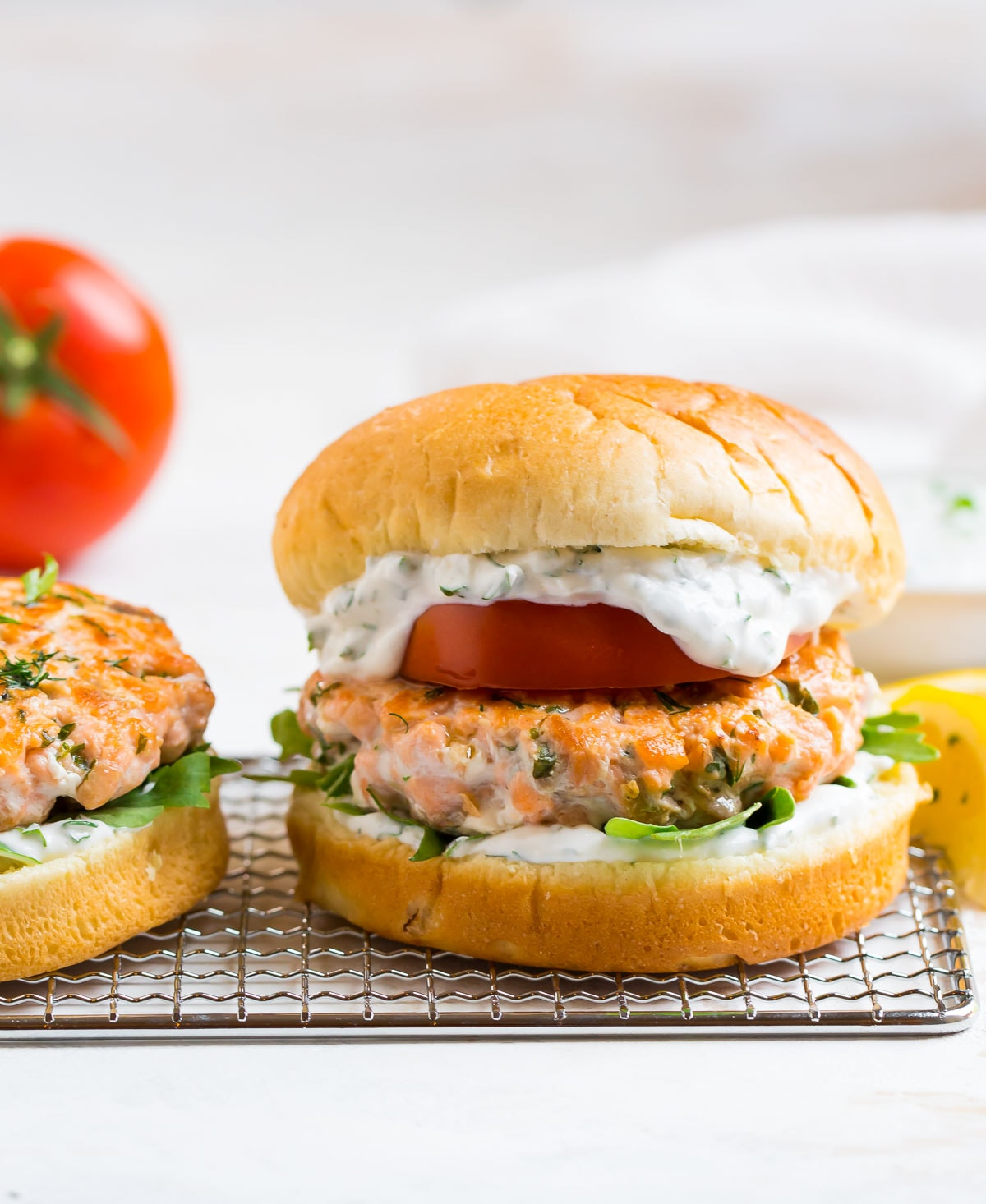 Salmon burgers with tomato, arugula, and sauce