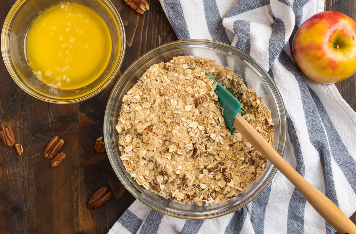 A mixing bowl with oats, pecans, flour, and a bowl of butter