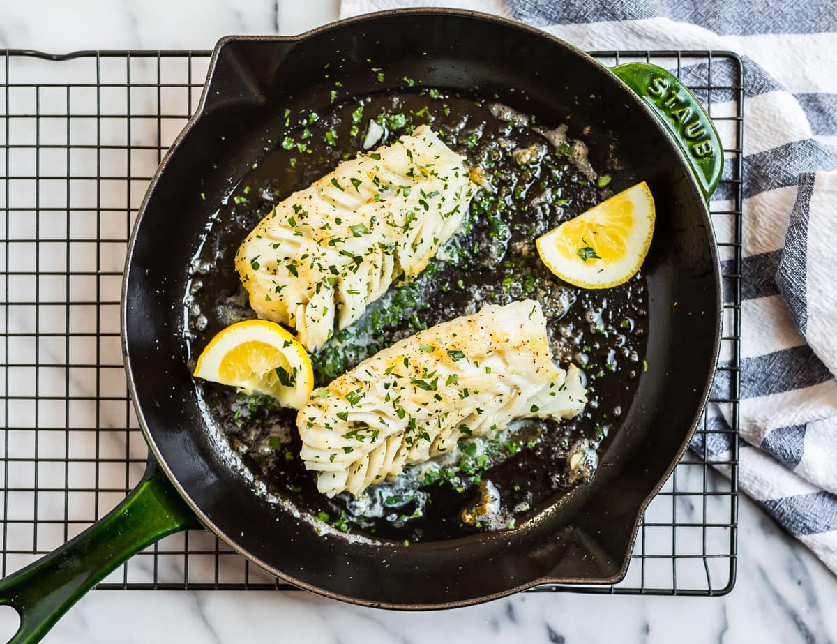 Cod fillets in a skillet with lemon