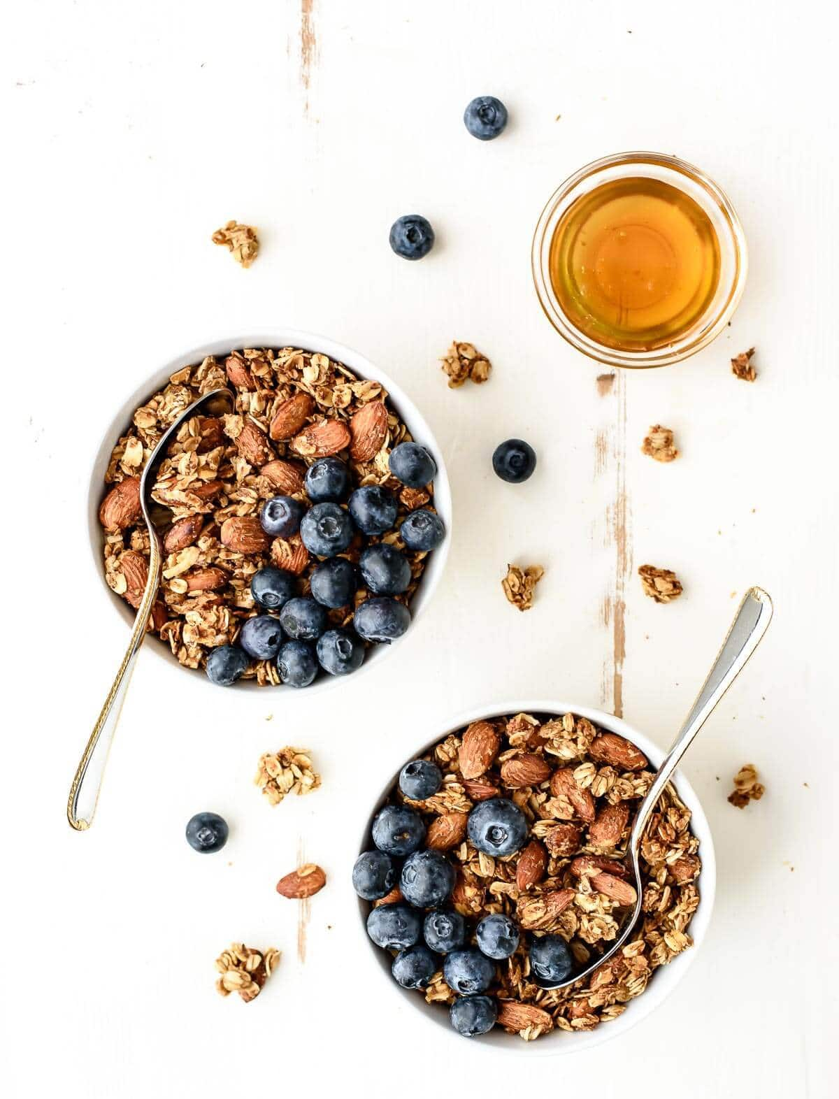 Two bowls of healthy granola with honey and blueberries