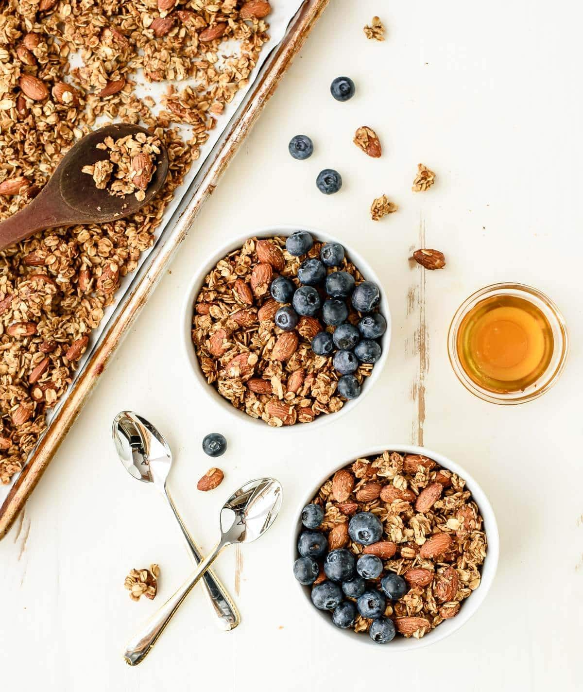 Two bowls of honey almond granola with blueberries