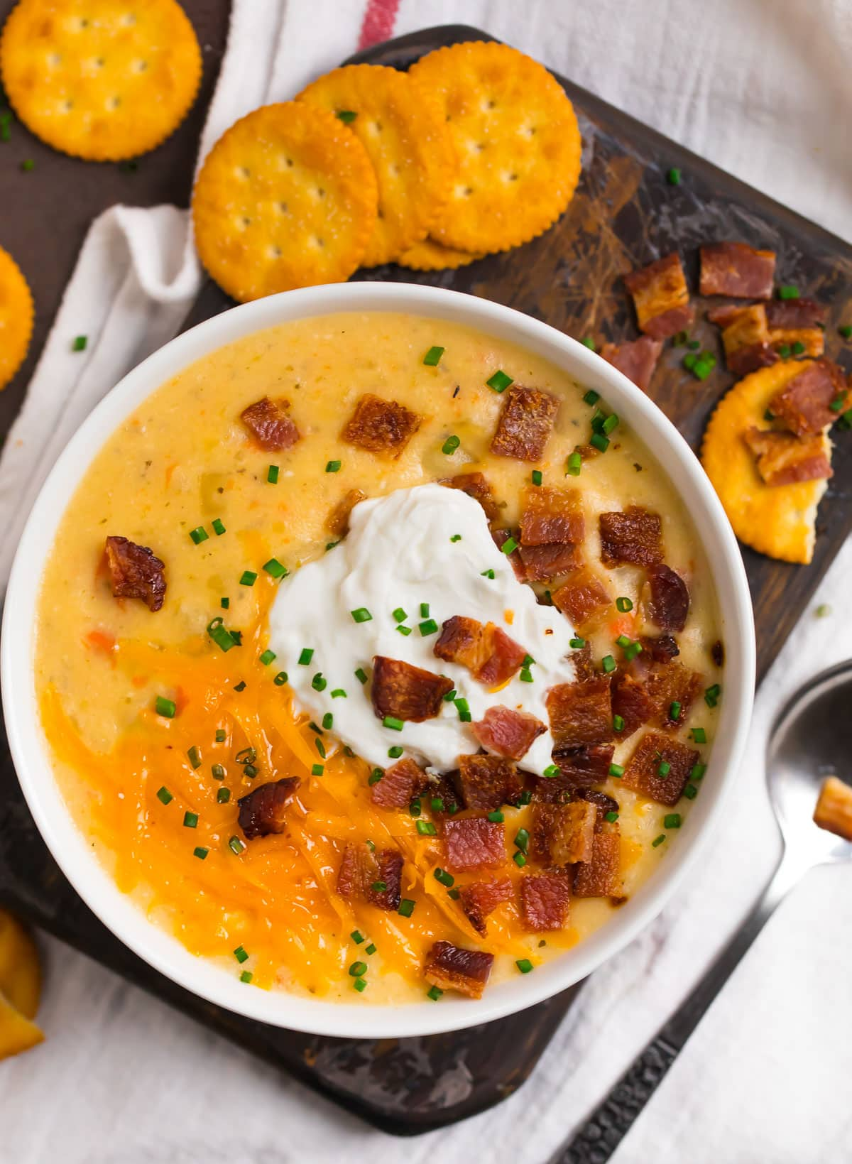 Crockpot potato soup in a bowl with bacon and cheese