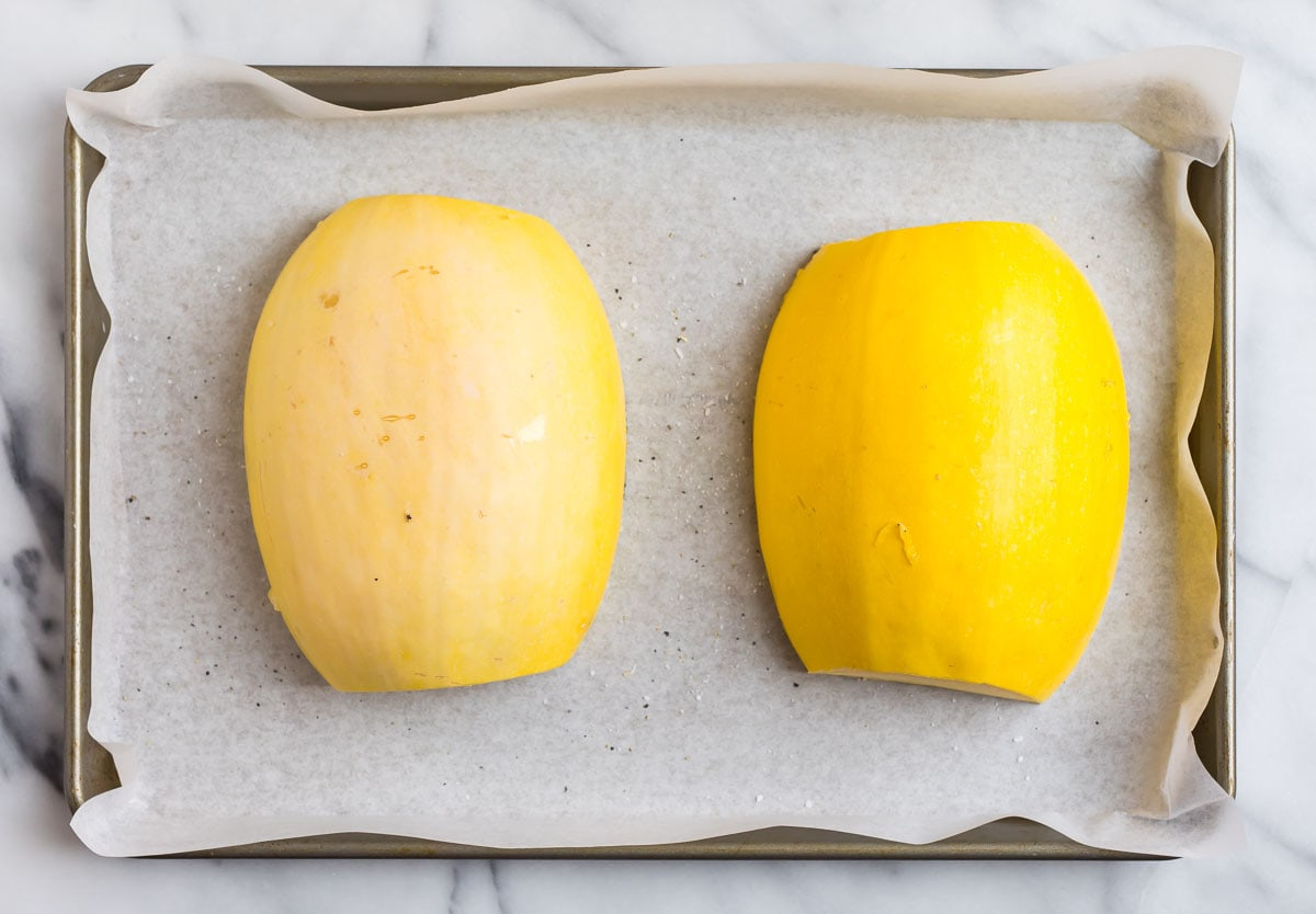 Two squash halves on a baking sheet