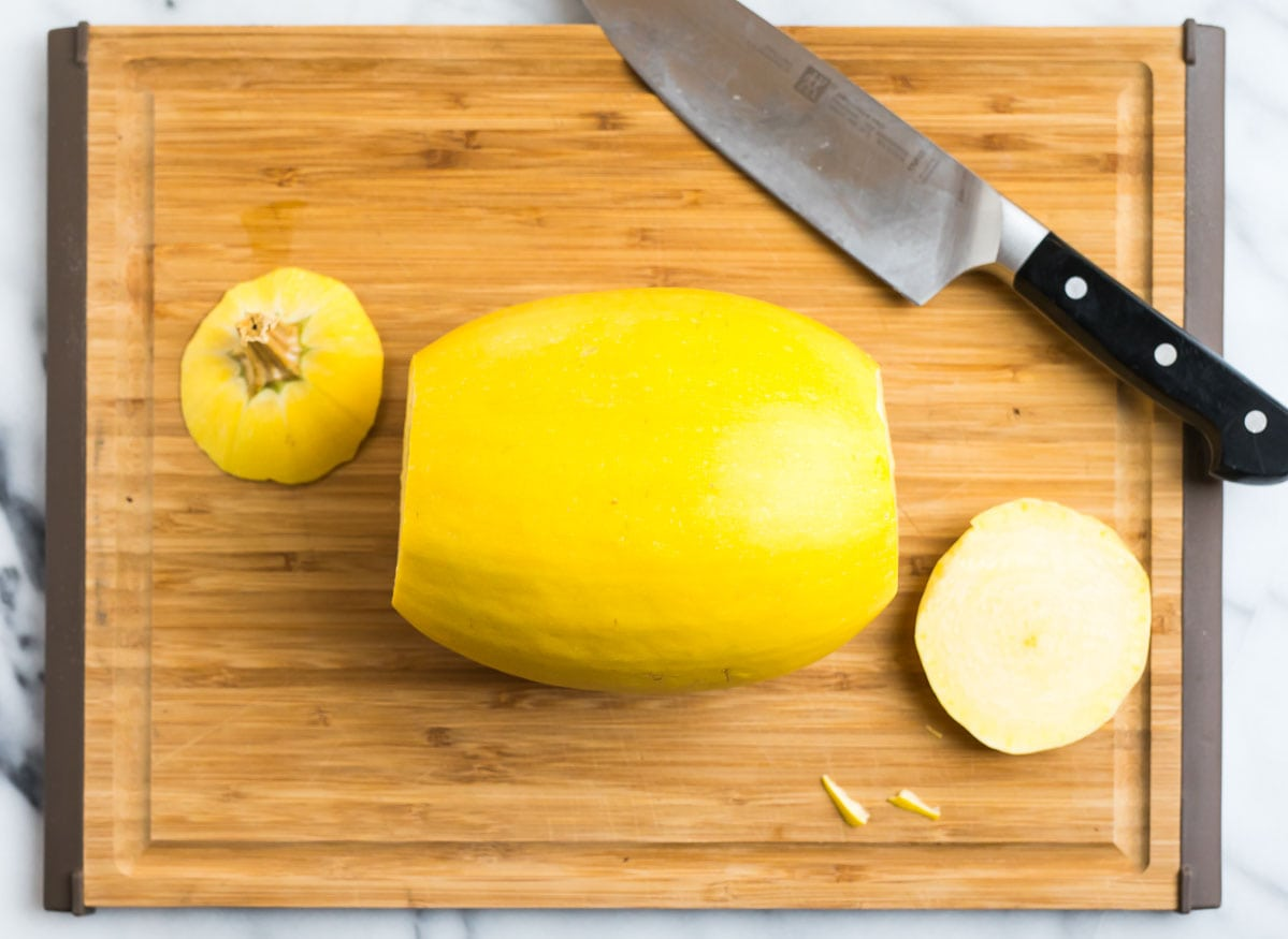 A vegetable being chopped on a cutting board