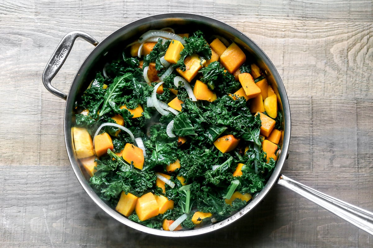 Squash cubes, kale, and onions in a skillet