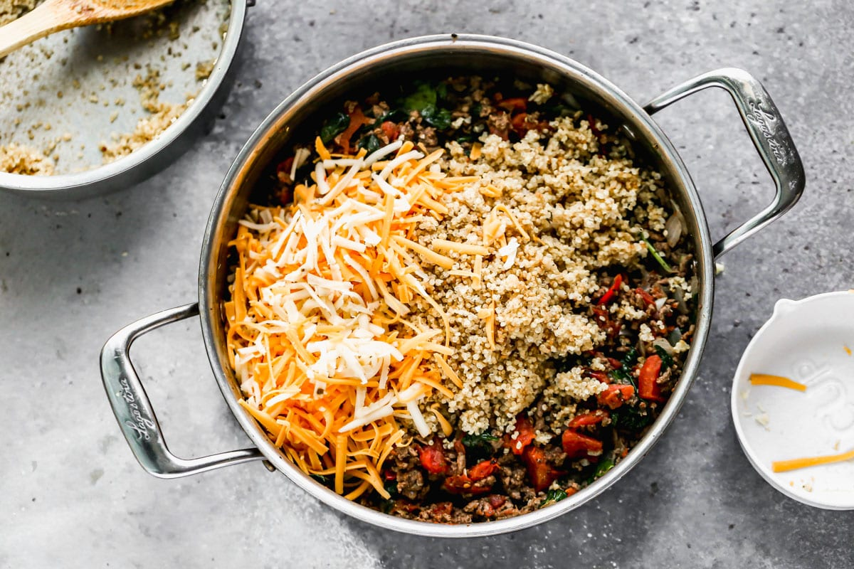 Cheese and quinoa being added to a skillet