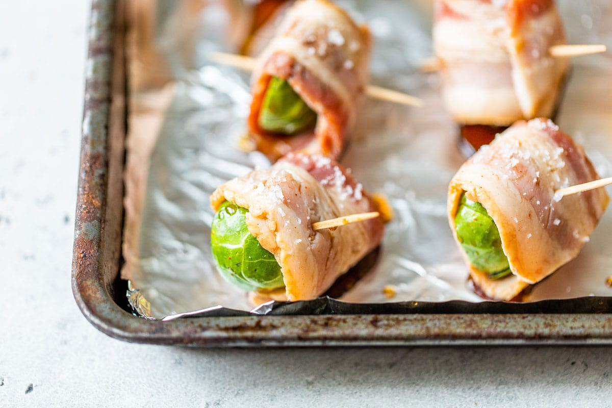 Bacon wrapped Brussels sprouts on a baking sheet with salt