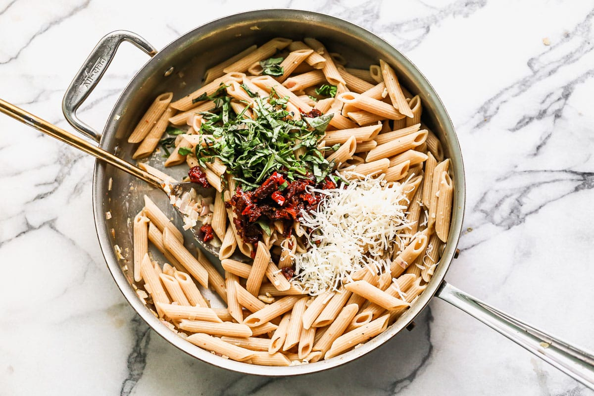 Noodles, cheese, red peppers, and herbs in a pot