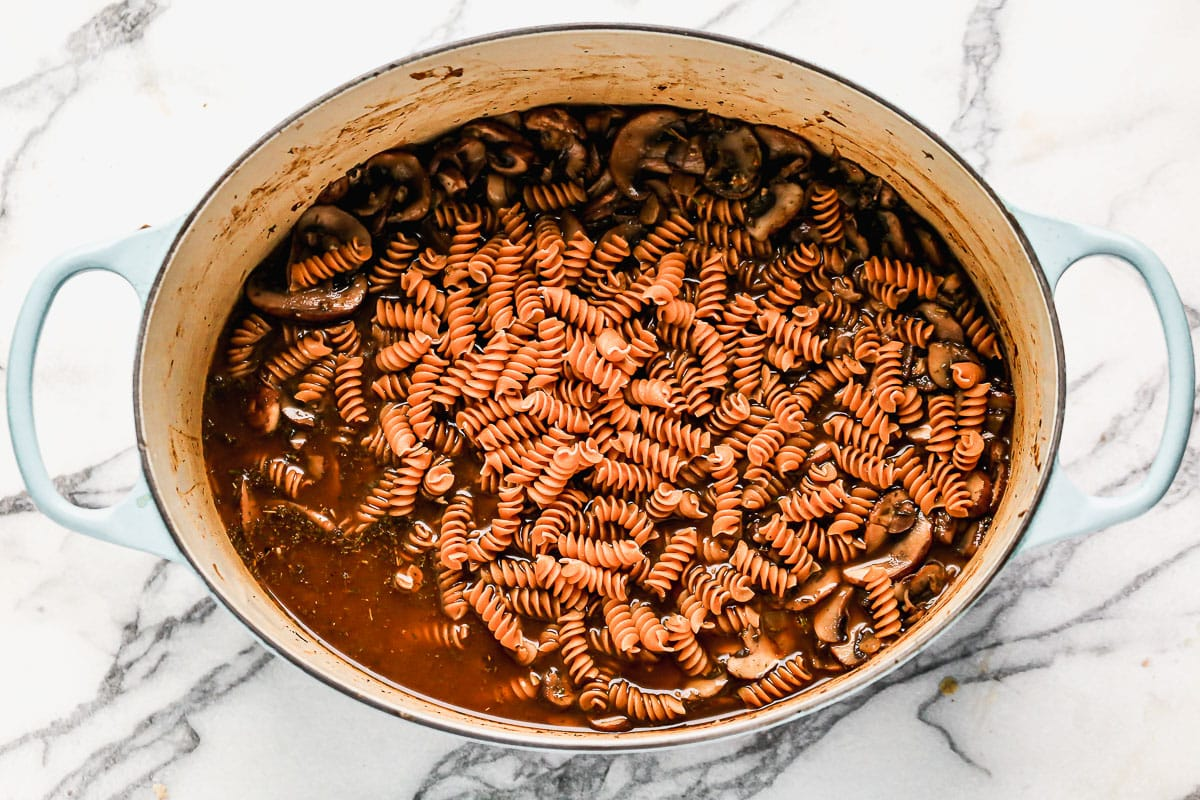 Pasta being added to a Dutch oven