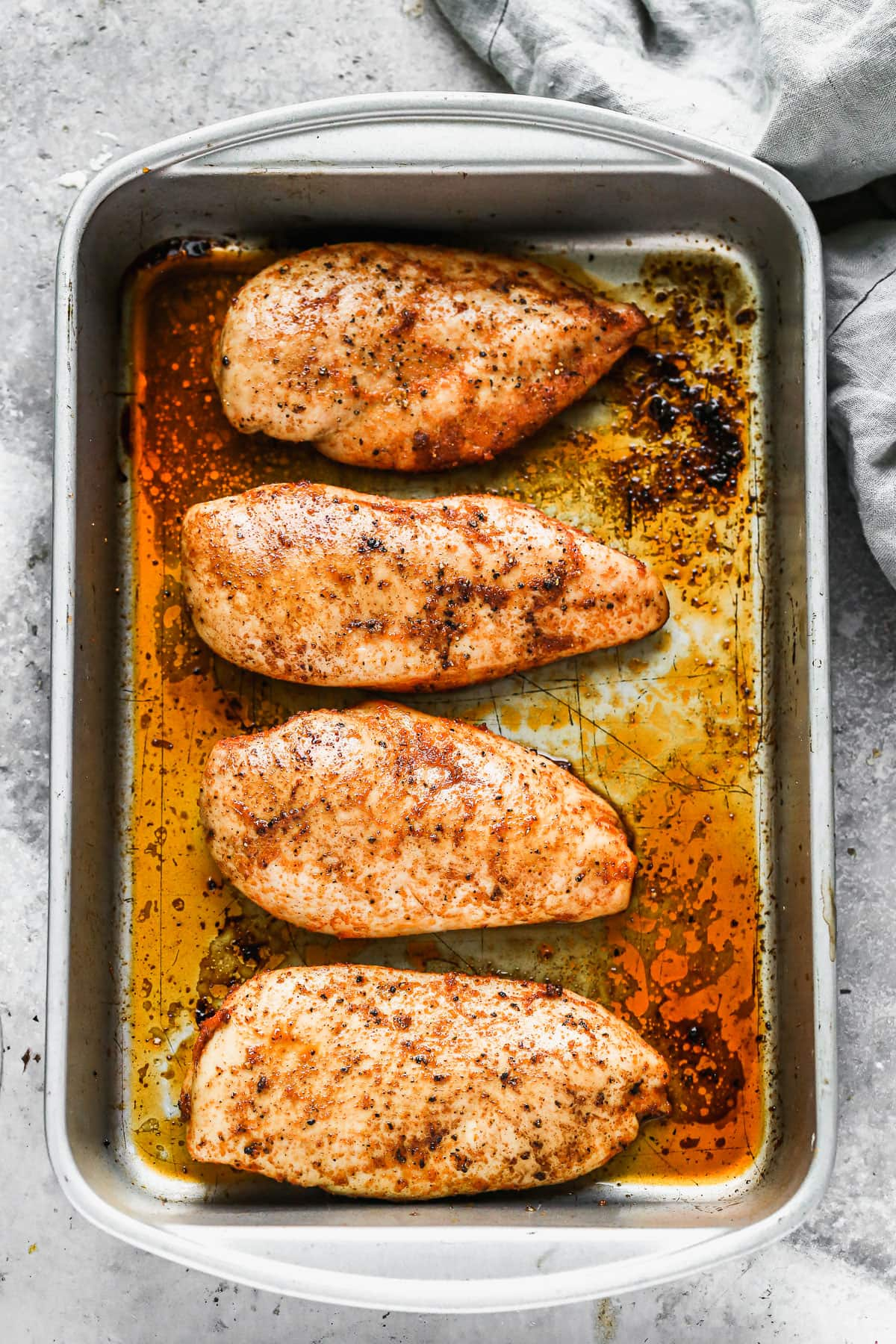 Four oven roasted chicken breasts in a pan