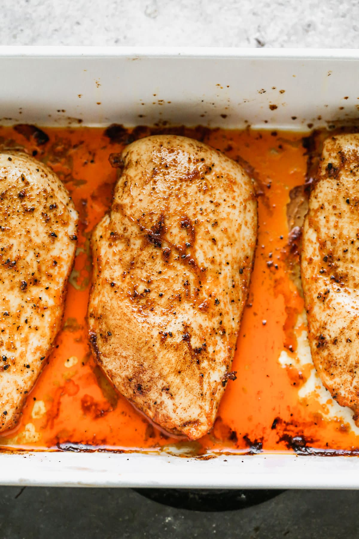 Three chicken breasts in a baking dish