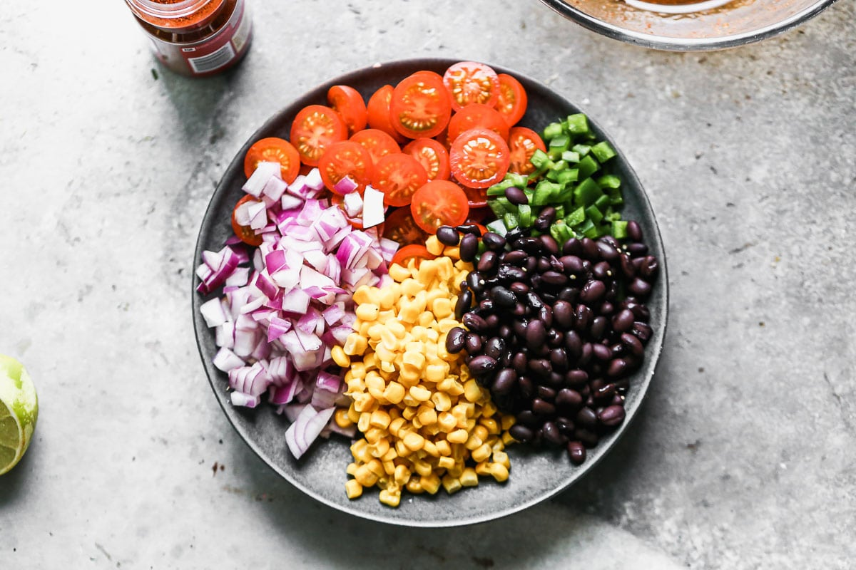 Red onion, tomato, corn, green pepper, and black beans on a plate