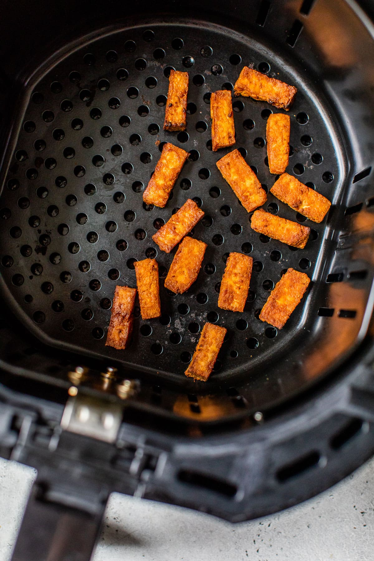 An air fryer basket with tofu