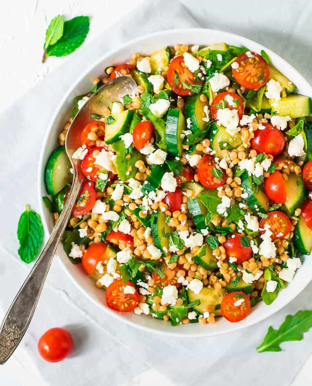 overhead photo of a bowl of Mediterranean Pearl Couscous Salad with a spoon for serving