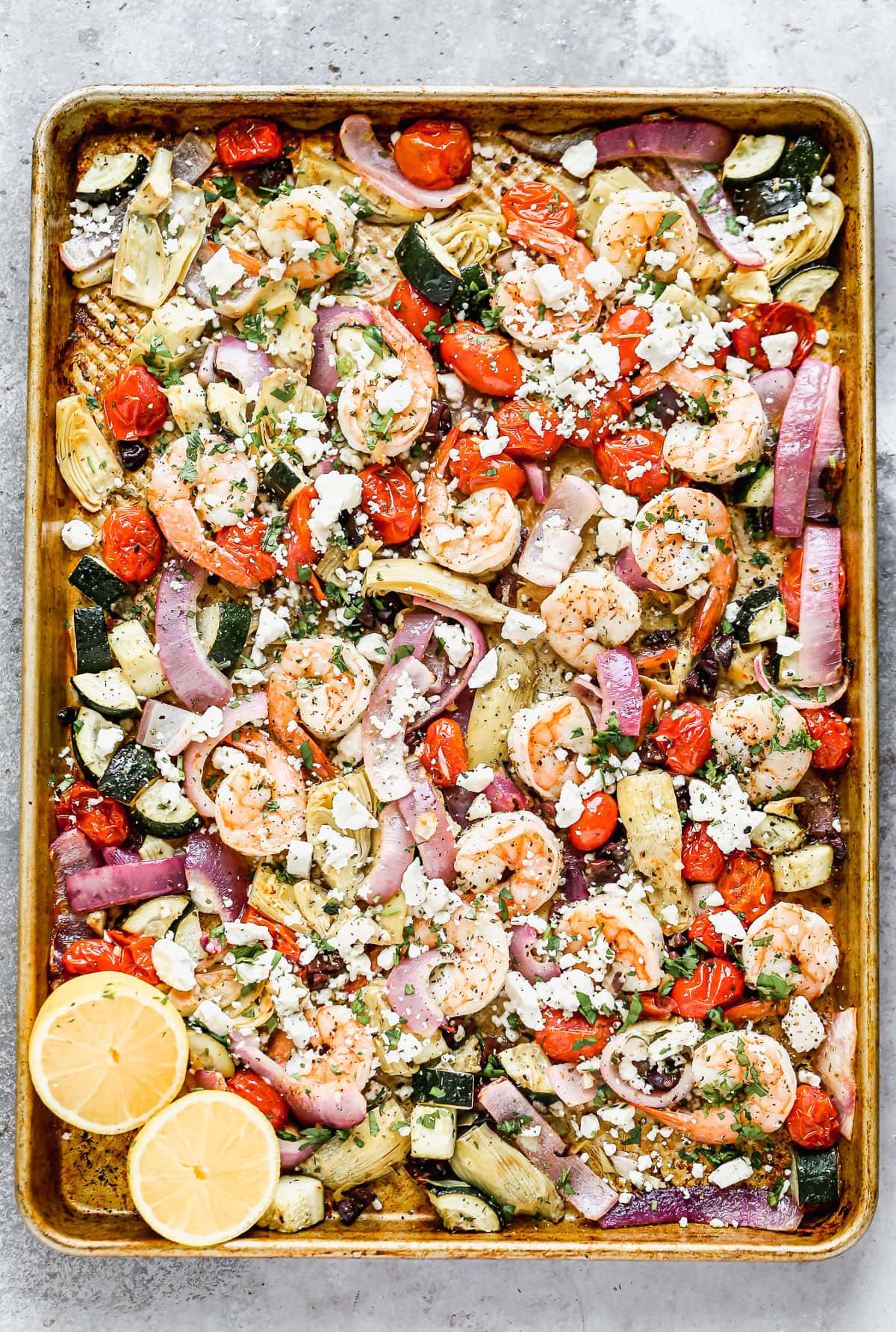 Shrimp, vegetables, and cheese on a baking sheet