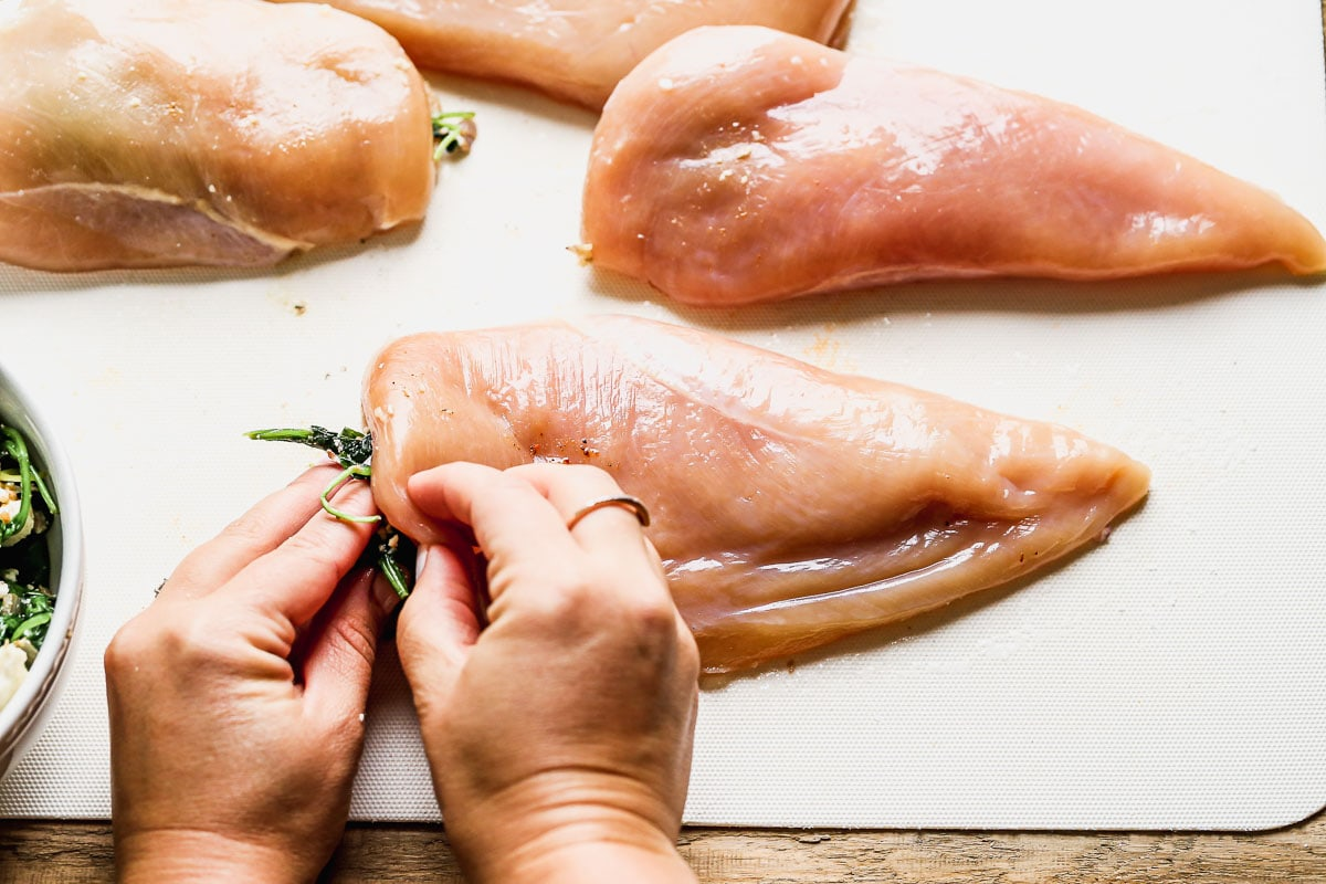 Chicken being stuffed with spinach