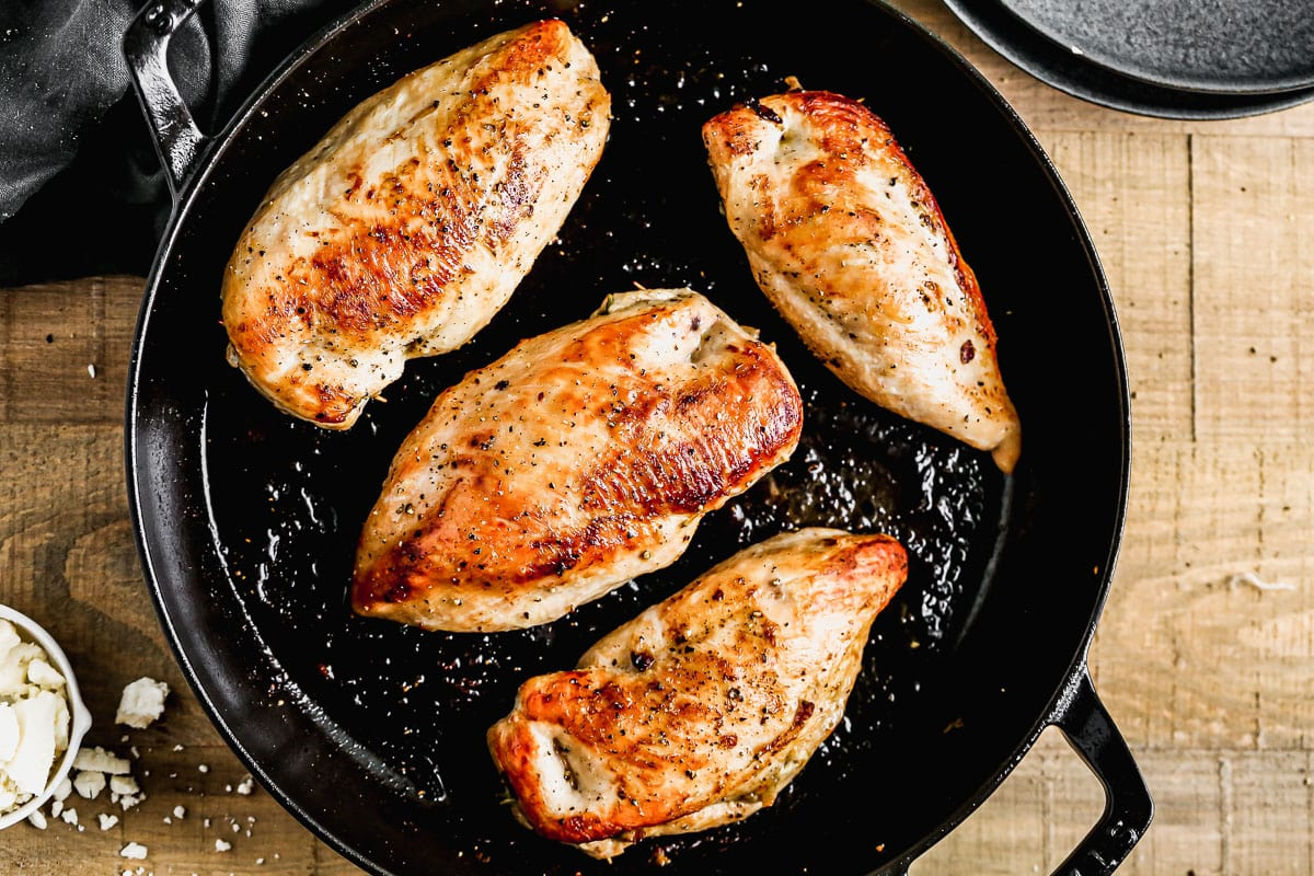 Spinach stuffed chicken breasts in a skillet